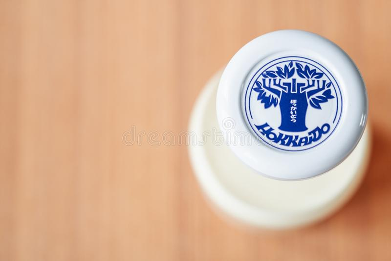 Парное молоко бренда Хоккаидо крупного плана в традиционной стеклянной бутылке на деревянном столе стоковое фото