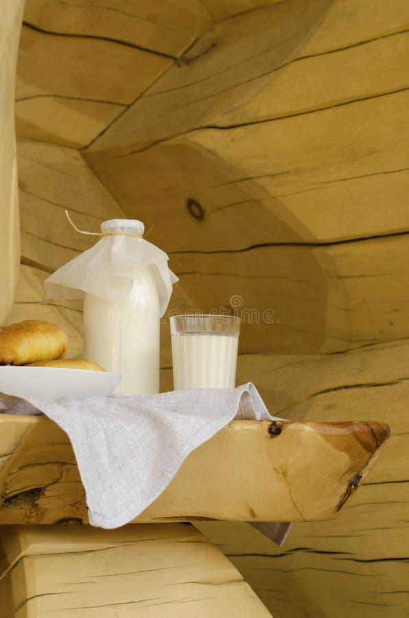 Парное молоко в стеклянной бутылке и стекле, рядом с пирогами на деревянном столе Концепция здоровых органических продуктов Ржавы стоковое изображение