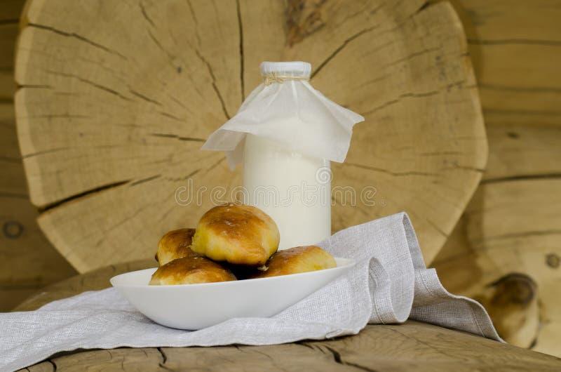 Парное молоко в стеклянной бутылке и стекле, рядом с пирогами на деревянном столе Концепция здоровых органических продуктов Ржавы стоковые изображения