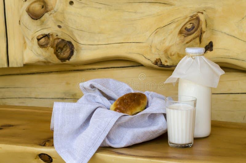 Парное молоко в стеклянной бутылке и стекле, рядом с пирогами на деревянном столе Концепция здоровых органических продуктов Ржавы стоковая фотография
