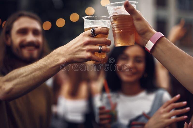 2 парня провозглашая тост с напитками алкоголя пока тратящ время outdoors стоковая фотография