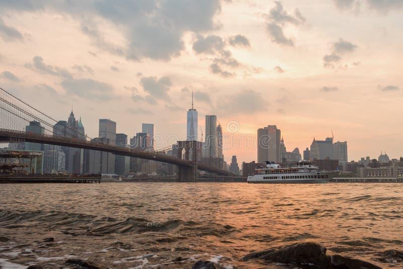 Паром НЬЮ-ЙОРКА - США - 12-ое июня 2015 проходя под мост Манхэттена стоковая фотография