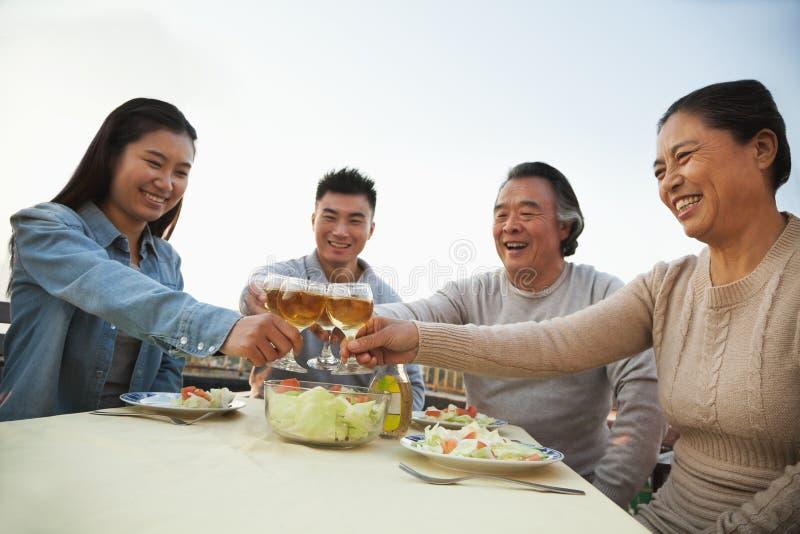 Партия барбекю семьи, провозглашать на таблице и усмехаться стоковое фото rf