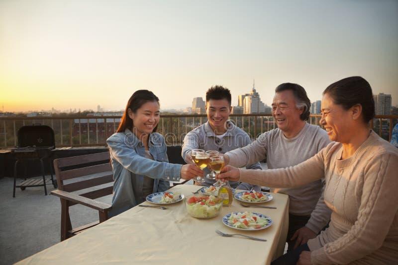 Партия барбекю семьи, провозглашающ тост на таблице, усмехаясь стоковые изображения