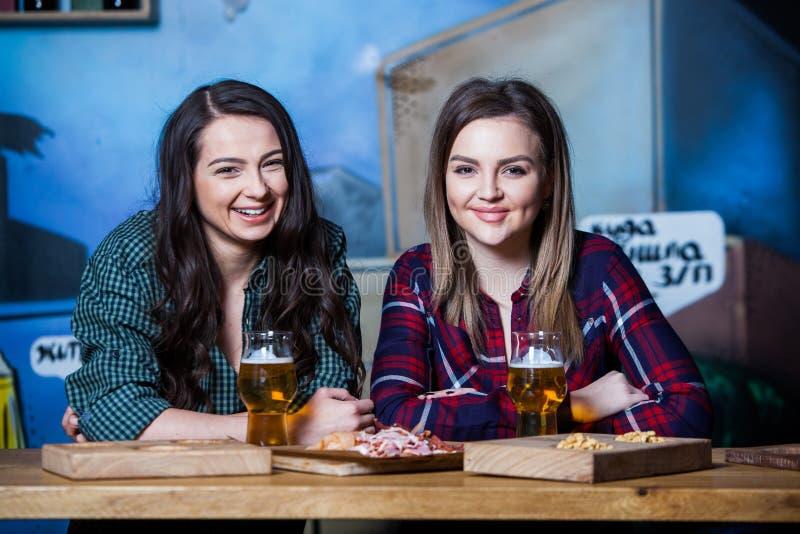 партия изображения девушок конструкции скача Красивые девушки выпивая пиво в баре Подруги провозглашать и есть в пабе стоковая фотография rf