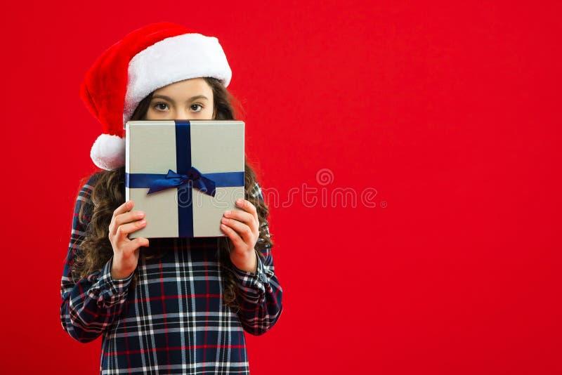 Партия Новый Год Ребенк Санта Клауса покупка рождества Настоящий момент для Xmas Детство Ребенок маленькой девочки в шляпе santa  стоковое фото rf