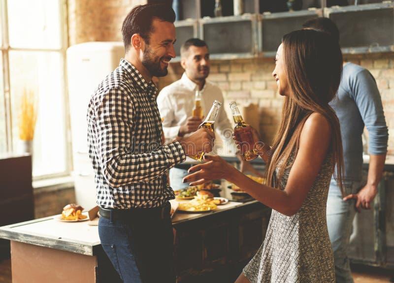 Партия с лучшими другами Группа в составе жизнерадостное молодые люди наслаждаясь домашней партией с закусками и пить пока связыв стоковое фото rf