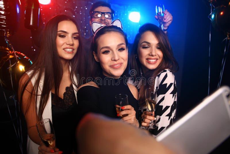 Партия, технология, ночная жизнь и концепция людей - усмехаясь друзья при smartphone принимая selfie в клубе стоковые изображения