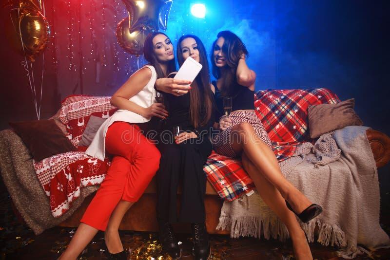 Партия, технология, ночная жизнь и концепция людей - усмехаясь друзья при smartphone принимая selfie в клубе стоковая фотография