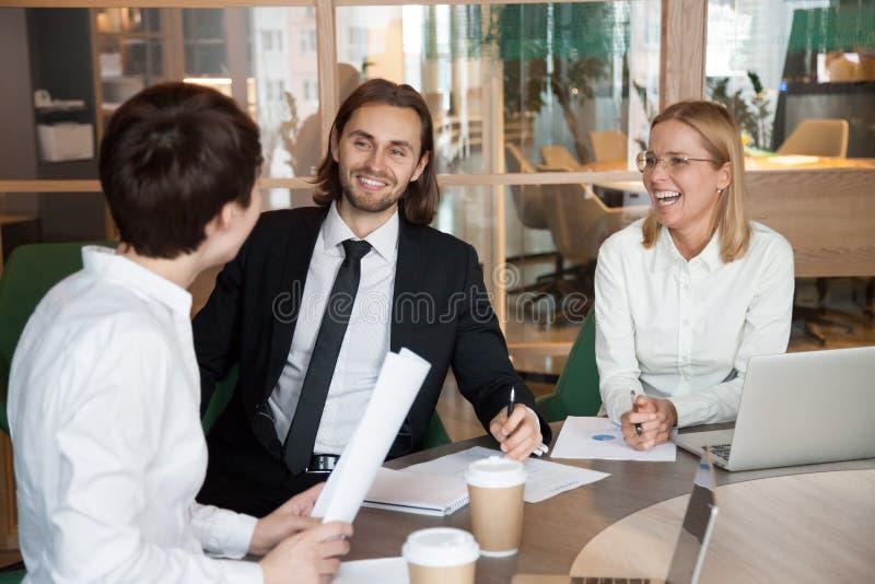 Партнеры имея дружелюбный переговор смеясь над во время дела m стоковые изображения rf