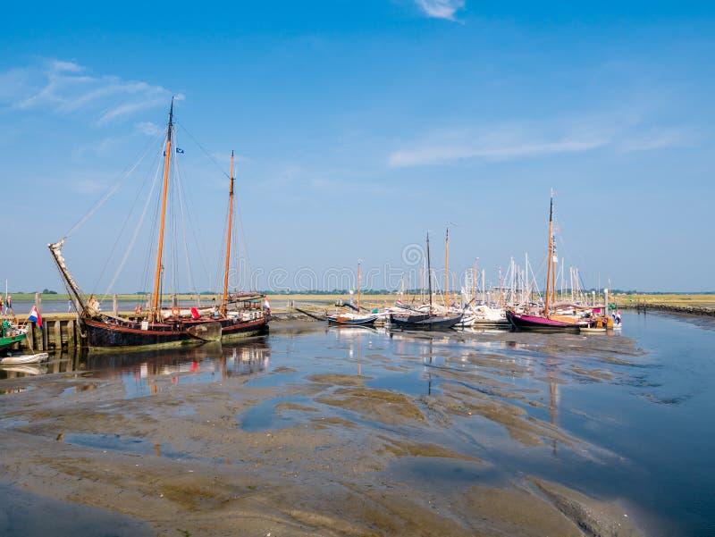Парусники в Марине во время отлива, западный остров Schiermonnikoog Frisian, Нидерланд стоковая фотография
