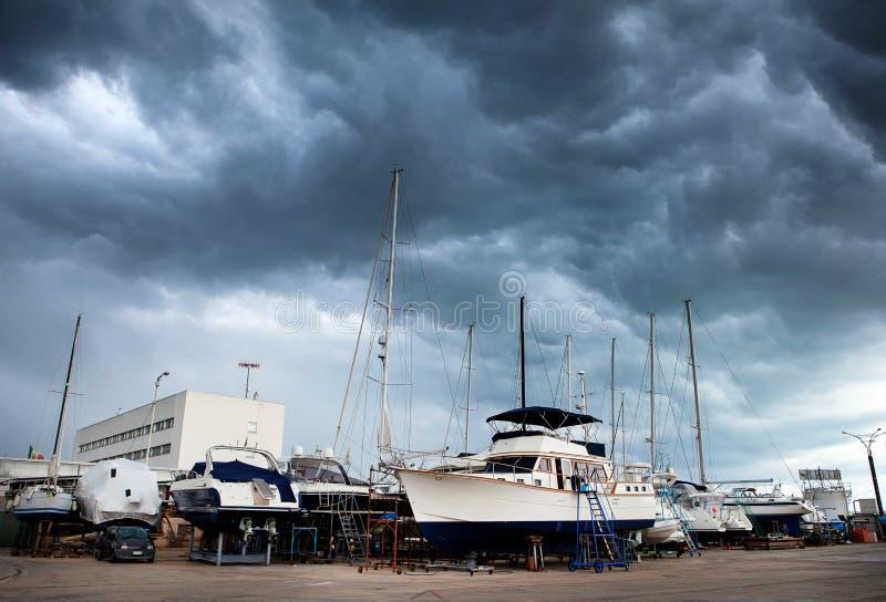 Парусники и моторные лодки в верфи для ремонта и обслуживания в Марине стоковое фото