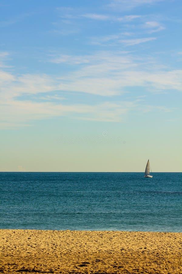 Парусник в расстоянии на пляже стоковое изображение rf