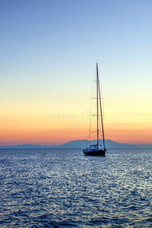 Парусник на море на заходе солнца, горах в предпосылке стоковые фотографии rf