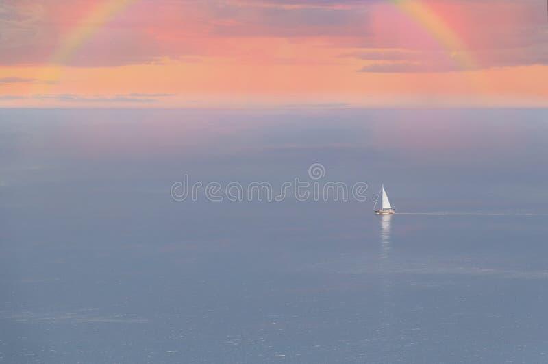 Парусник на море под радугой стоковое изображение