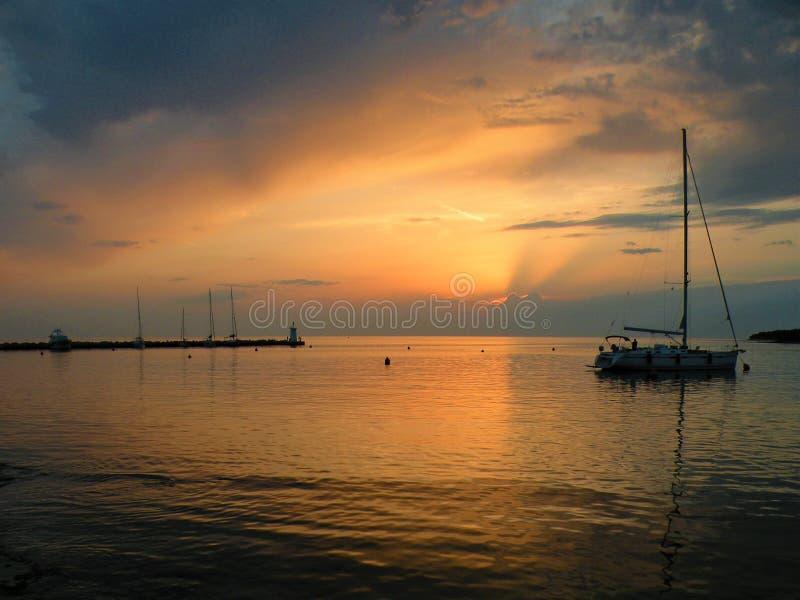 Парусник плавая на мирную поверхность theAdriatic моря, Хорватии, Европы Заход солнца и штиль на море с красивым пурпурным небом стоковая фотография rf