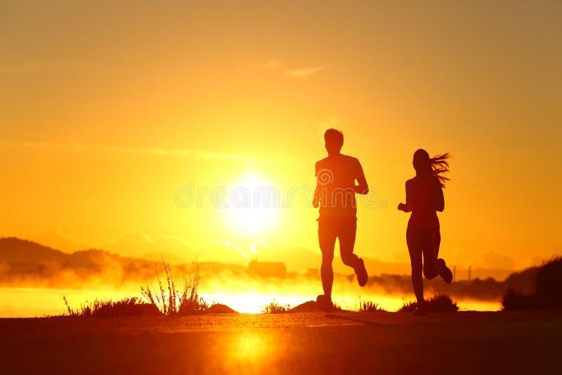 Пару шилуэтов, бегающих на рассвете на пляже стоковая фотография