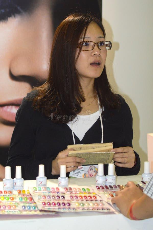 Парфюмерия Intercharm XXI международная и выставка косметик стоят член команды Маникюр, ложные ногти Женщина стоковые фотографии rf