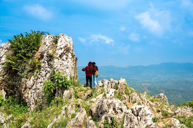 Пары альпиниста утеса празднуя и наслаждаясь их достижение вверху гора со сценарным взглядом ландшафта ниже стоковое изображение