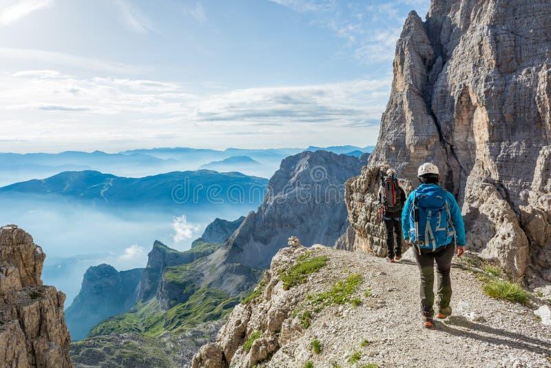 Пары альпинистов идя путь горы стоковые изображения