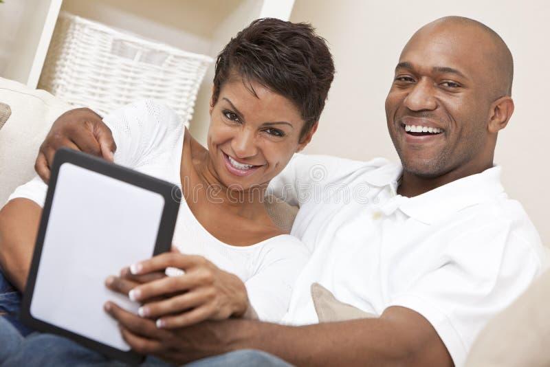 Пары афроамериканца используя компьютер таблетки стоковая фотография rf