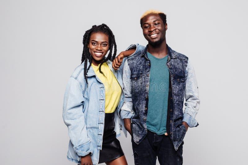 Пары Афро американские в вскользь одеждах усмехаясь на камере на белой предпосылке стоковые изображения rf