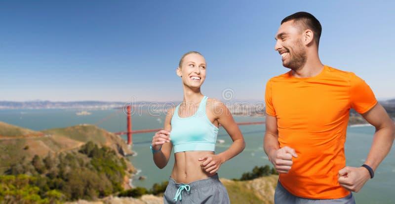 Пары бежать над предпосылкой моста золотого строба стоковое фото