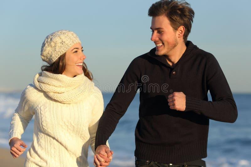 Пары бежать на пляже в зиме стоковая фотография rf