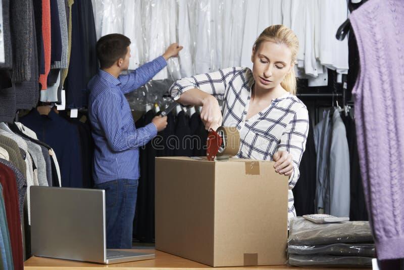 Пары бежать онлайн товары упаковки магазина одежды для отправки стоковые изображения