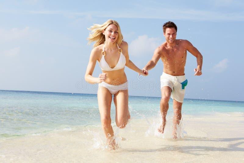 Пары бежать через волны на празднике пляжа стоковая фотография rf