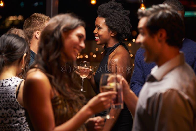Пары беседуя и выпивая на партии вечера стоковые фотографии rf
