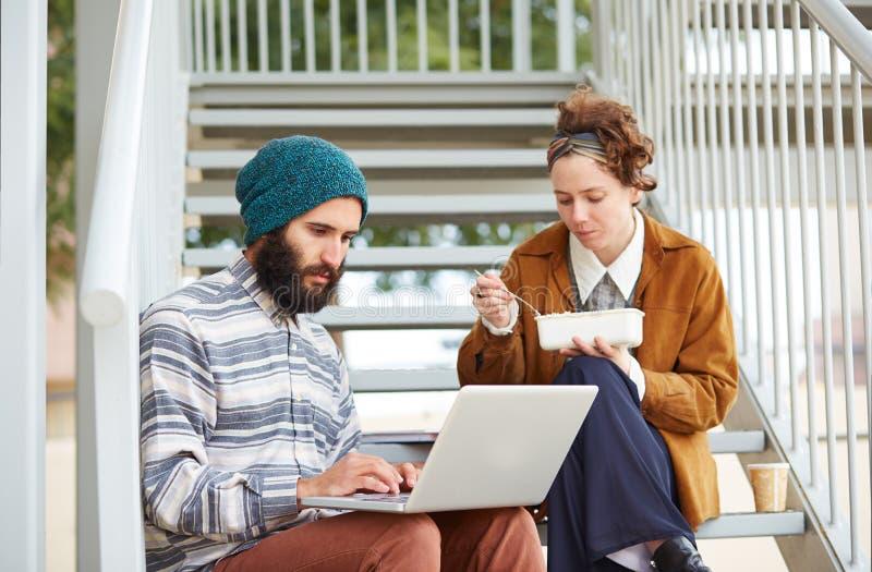 Пары битника используя компьютер и есть обед outdoors стоковое фото