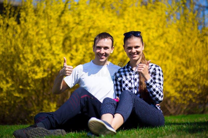 Пары влюбленн в большие пальцы руки вверх отдыхая в парке на свежей зеленой траве стоковые изображения rf