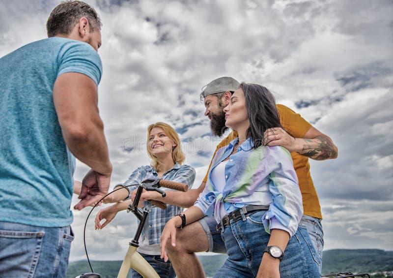 Пары встречают жизнерадостных друзей с велосипедом во время прогулки Задействуя современность и национальная культура Молодая ком стоковое фото