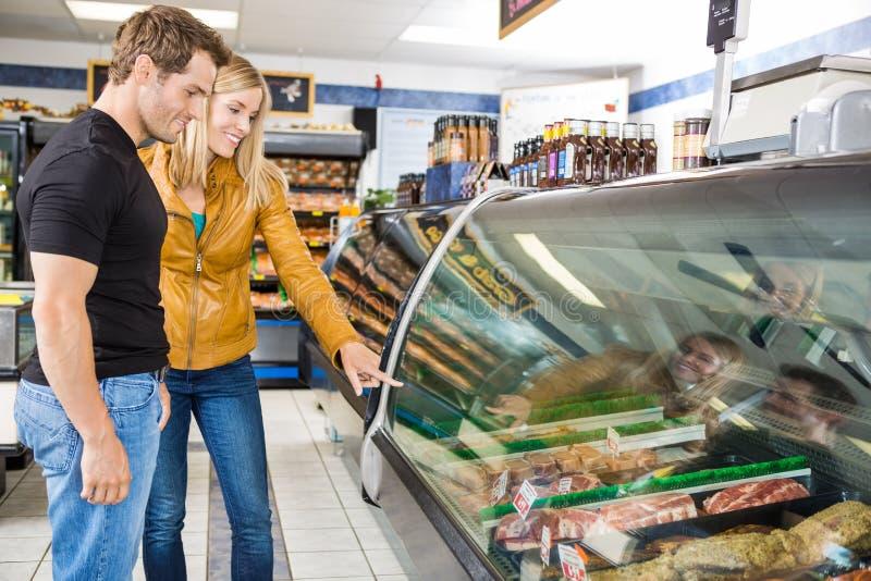 Пары выбирая мясо на магазине мясника стоковое фото rf