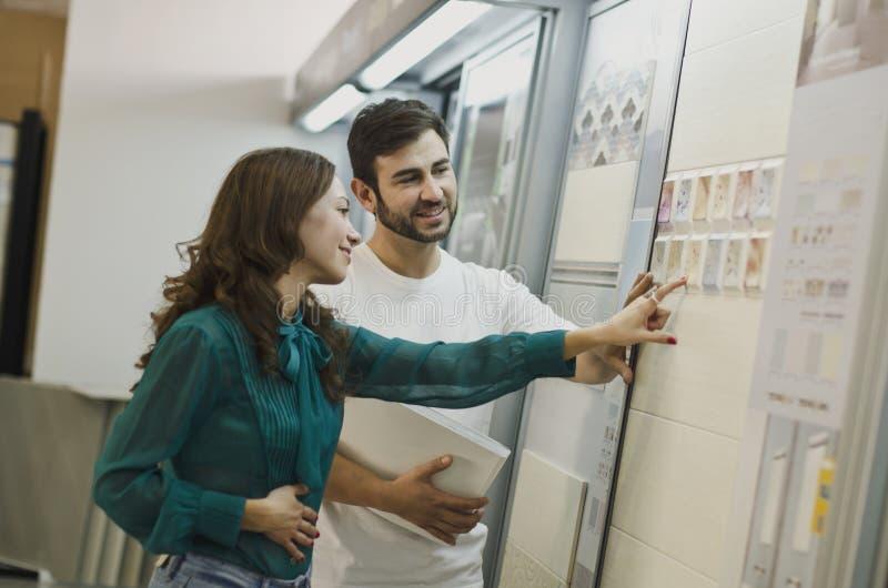 Пары выбирая плитки в магазине керамических и мебели для нового дома стоковые изображения