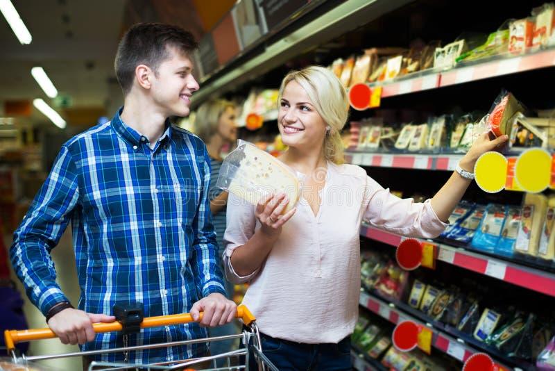Пары выбирая сыр на магазине стоковые фото