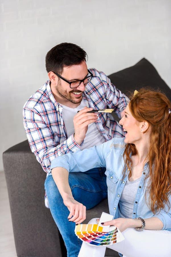 Пары выбирая цвета для крася дома; иметь потеху стоковые фото
