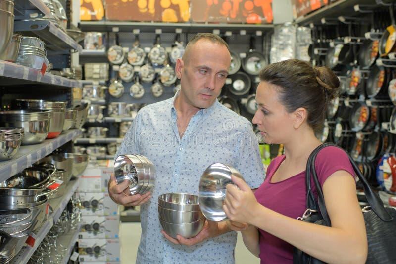Пары выбирая kitchenware на супермаркете стоковые фото