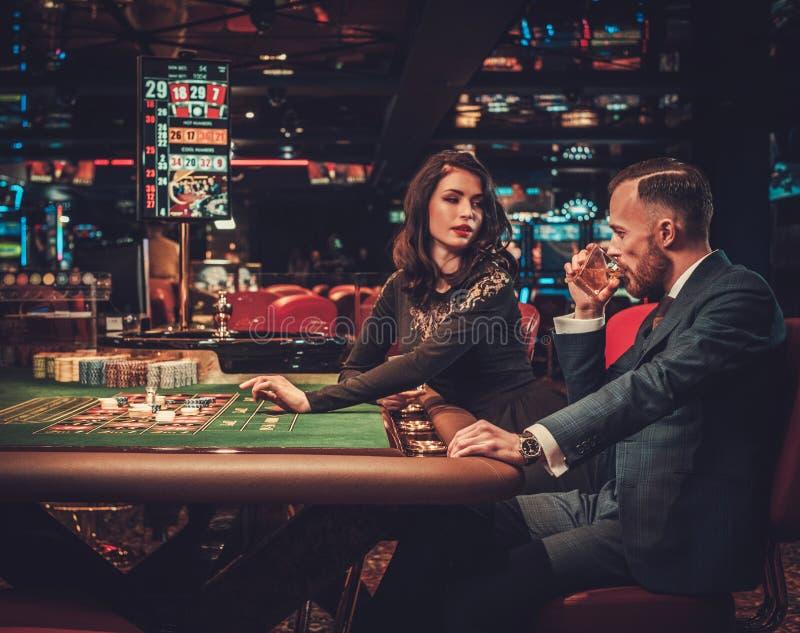 Пары высшего класса играя в азартные игры в казино стоковые фото