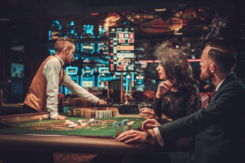 Пары высшего класса играя в азартные игры в казино стоковая фотография rf