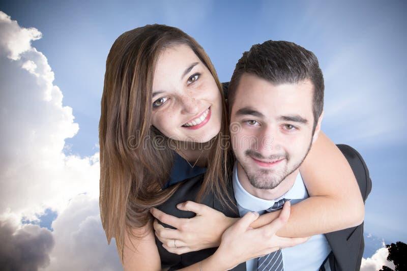 Пары в автожелезнодорожных перевозках женщины человека любов кавказских на его задней части под облаками голубого неба белыми стоковое фото rf