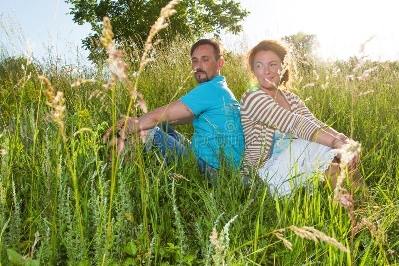 Пары в большой зеленой траве спина к спине Человек и женщина сидя в поле в летнем дне любящее пар gossipin нежно мирно стоковые изображения rf
