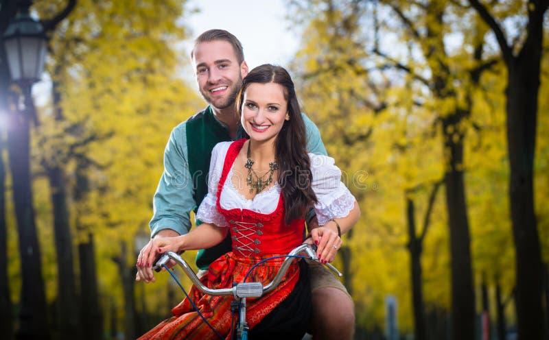 Пары в брюках Dirndl и кожи совместно на велосипеде стоковое фото rf
