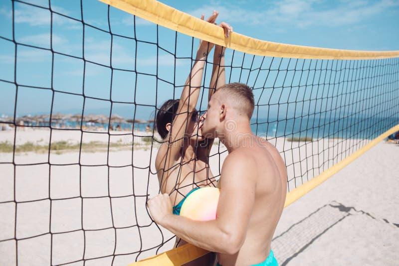 Пары в влюбленности играют волейбол на солнечном пляже Летние каникулы и перемещение на празднике в Майами Влюбленность и flirtin стоковые фото