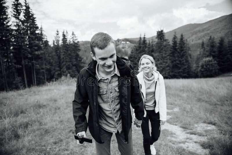 Пары в влюбленности идя в горы, имеющ потеху стоковая фотография