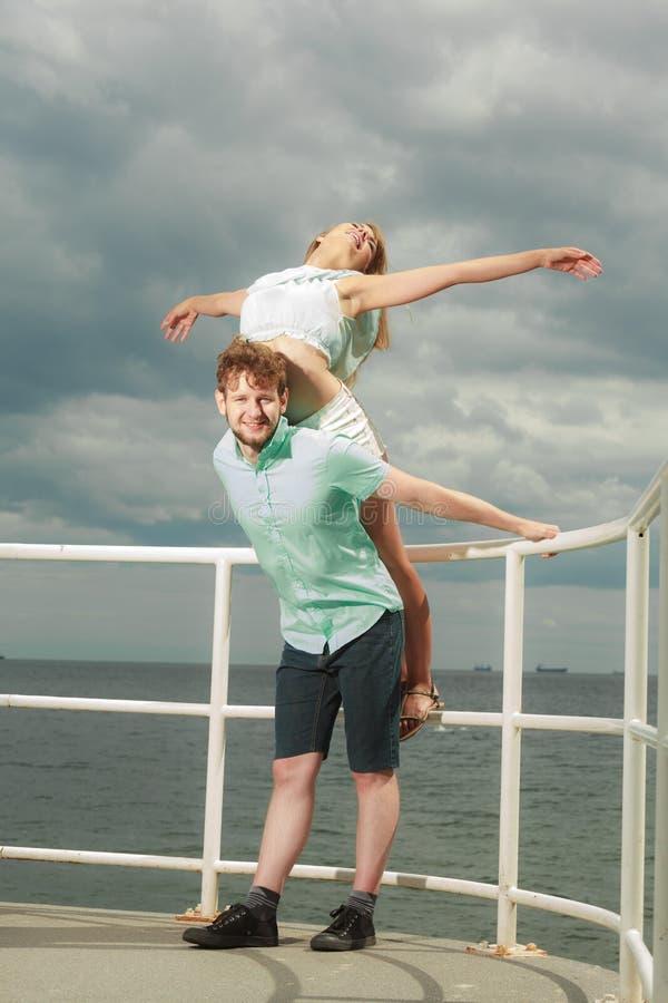 Пары в влюбленности имея потеху на пристани моря стоковое изображение