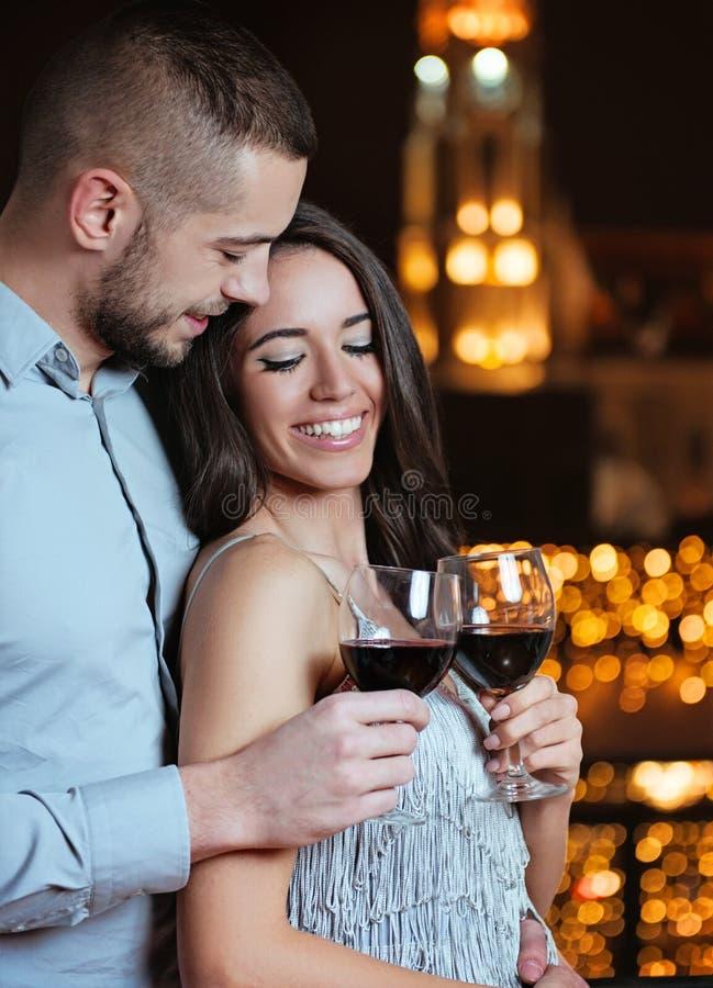 Пары в влюбленности, обнимая и наслаждаясь в красном вине стоковое фото rf