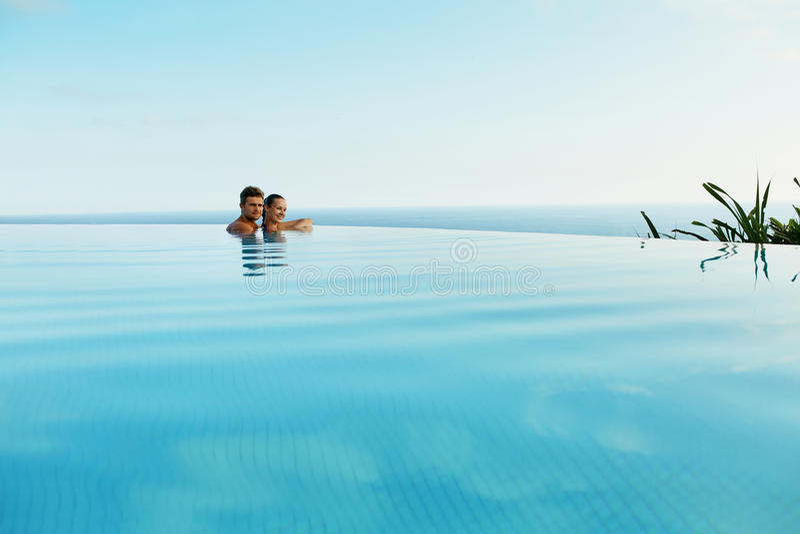 Пары в влюбленности в бассейне роскошного курорта на романтичных летних каникулах стоковые изображения