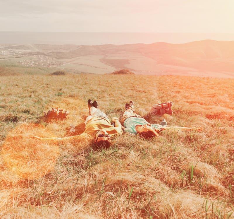Пары в влюбленности лежа на луге стоковые фотографии rf